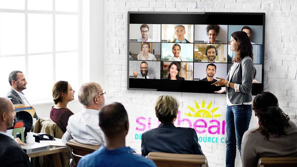 People gathered around a big screen TV in a Workshop setting